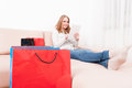 Smiling lady shopper holding tablet laying on couch Royalty Free Stock Photo