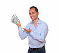 Smiling latin adult man holding cash dollars portrait of a looking at you and on isolated background Royalty Free Stock Images
