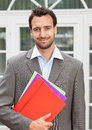 Smiling latin businessman with paperwork handsome in a grey suit colorful in front of his office Stock Photos