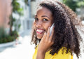 Smiling latin woman with curly hair at phone in summer Royalty Free Stock Photo