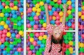 Smiling little Asian child girl playing climb and hanging on cage of playground colorful toy ball with looking camera Royalty Free Stock Photo