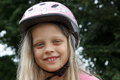 Smiling little bicyclist girl with a helmet on his head Stock Images