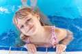 Smiling little blond girl in a pool Stock Photos
