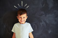 Smiling little boy against chalk drawing of exclamation marks