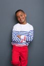 Smiling little boy with arms crossed portrait of a posing against gray background Stock Images