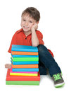 Smiling little boy with books a sits on the floor near the pile of on the white background Stock Photos