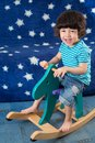 Smiling little boy have fun on a toy horse in room with blue sofa with stars Stock Photos