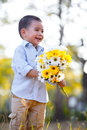 Smiling little boy holing flowers standing in park outdoor portrait Stock Photography