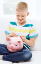 Smiling little boy with piggy bank and money childhood investment happy people concept at home Stock Image