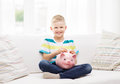 Smiling little boy with piggy bank and money childhood investment happy people concept at home Royalty Free Stock Photography