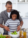 Smiling little boy preparing salad with his father Royalty Free Stock Photo
