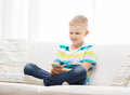 Smiling little boy with smartphone at home leisure technology and internet concept Stock Photos