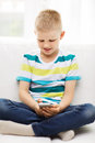 Smiling little boy with smartphone at home leisure technology and internet concept Royalty Free Stock Image