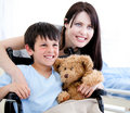 Smiling little boy in a wheelchair with his mother Stock Images