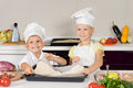 Smiling little cooks preparing a homemade pizza in white chefs uniforms for their lunch placing the rolled dough onto baking Stock Photography