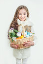 Smiling little girl with basket full of colorful easter eggs and flowers spring Stock Photography