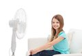 Smiling little girl with big fan at home summer weather and equipment concept sitting on sofa Stock Images