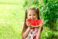 Smiling little girl with blue eyes eats a slice of watermelon Royalty Free Stock Photo