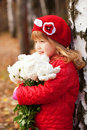 Smiling little girl with bouquet of white flowers happy for the mother looking the side Royalty Free Stock Images