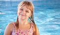 Smiling little girl with bright blue pool water Royalty Free Stock Photography