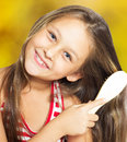 Smiling little girl brushing her hair on a golden background Royalty Free Stock Images