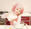 Smiling little girl with chef hat put flour for baking cookies in the kitchen Stock Images