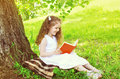 Smiling little girl child reading a book on the grass near tree Royalty Free Stock Photo