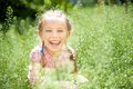 Smiling little girl cute on the meadow in sunny day Stock Images
