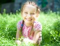 Smiling little girl cute on the meadow in sunny summer day Royalty Free Stock Image