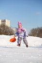 Smiling little girl dressed in pink scarf and hat runs with saucer at winter Royalty Free Stock Photography