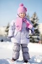 Smiling little girl dressed in pink scarf and hat stands looks away at winter Stock Image