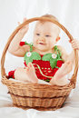 Smiling little girl dressed in strawberry suit sitting in basket portrait of wicker on white coverlet Stock Image
