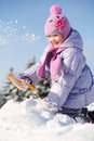 Smiling little girl dressed in warm clothes throws snow by shovel on pile of at winter Royalty Free Stock Photos