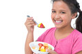 Smiling little girl eating fruit salad on white background Royalty Free Stock Image