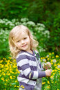 Smiling little girl with flower in her hands vertical portrait of a beautiful blond summer day Royalty Free Stock Image