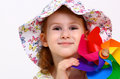 Smiling little girl in hat playing with windmill toy on white Stock Image