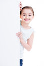 Smiling little girl holding empty white banner isolated on Stock Photography