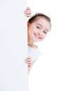 Smiling little girl holding empty white banner isolated on Stock Photos