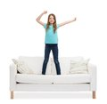 Smiling little girl jumping or dancing on sofa Royalty Free Stock Photo