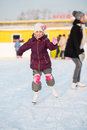 Smiling little girl in knee pads skating at the rink winter Stock Image