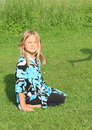 Smiling little girl kneeing on grass in blue black white t shirt green Royalty Free Stock Photography
