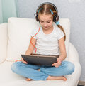 Smiling little girl listening something with headphones Royalty Free Stock Photo