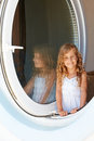 Smiling little girl look into window in white dress made in form of porthole Stock Image