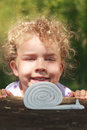 Smiling little girl with lovely curly blond hair beautiful wonderful crouched low looking at a coiled toy snail on an outdoor Royalty Free Stock Photography