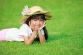 Smiling little girl lying on green grass Royalty Free Stock Photography