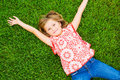Smiling little girl lying on green grass cute relaxing enjoying the vacation Royalty Free Stock Images
