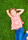 Smiling little girl lying on green grass cute relaxing expressions Royalty Free Stock Image