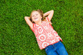Smiling little girl lying on green grass cute relaxing face Stock Photos