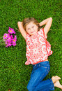 Smiling little girl lying on green grass with flowers cute relaxing in peace Royalty Free Stock Photos