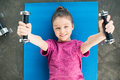 Smiling little girl lying on mat and exercising with dumbbells Royalty Free Stock Photo